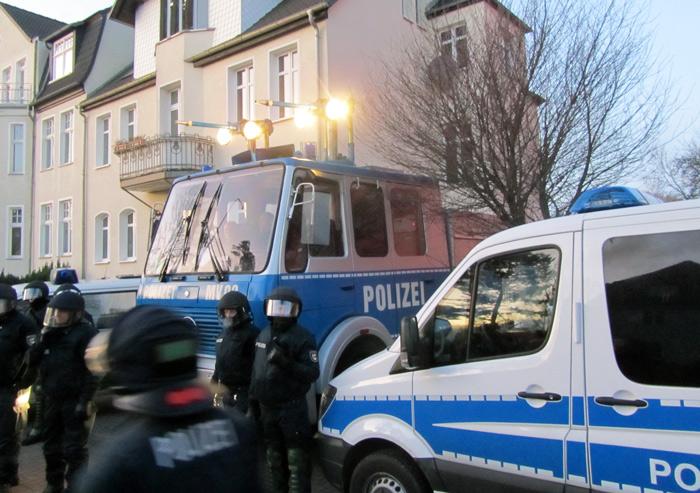 Drohkulisse: Wasserwerfer und Einsatzfahrzeuge setzen Hausarrest um